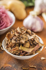 Dried mushrooms sour cabbage garlic and potatoes on wooden table