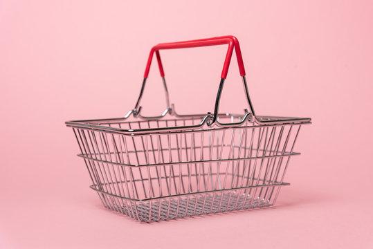 Shopping basket on pink background