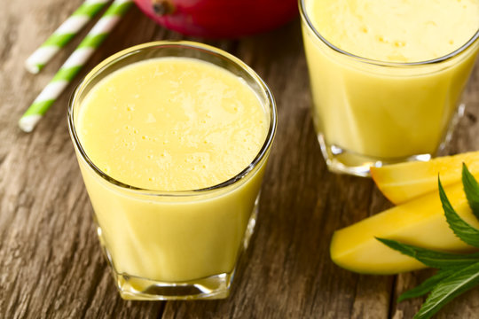 Refreshing mango and yogurt smoothie in glasses with straw (Selective Focus, Focus one third into the first drink)
