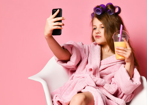 Young cheeky lady teen girl in bathrobe and with hair in curlers drinks smoothie fresh juice and takes cool fashion look selfie on pink