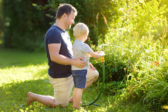 Funny little boy with his father playing with garden hose in sunny backyard. Preschooler child having fun with spray of water.