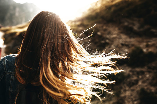 Unrecognizable back view of a female long hair brown playing in the sun flares in the morning against sun.