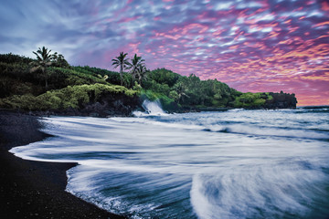 Black Sand Beach with Sunrise, Purple Sky, Waves, Green Vegetation and Lava Rocks in Maui, Hawaii.