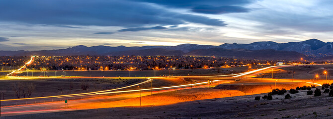 Sunset Highway - A panoramic dusk view of U.S. Highway 285 winding at the foothill of Front Range of Rocky Mountains on a stormy winter evening. Southwest of Denver, Colorado, USA. Wall mural