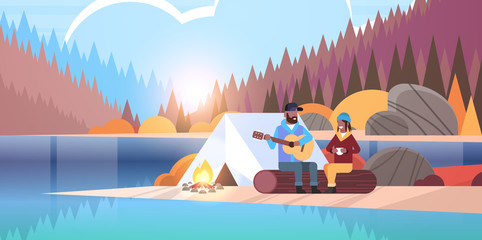 couple tourists hikers relaxing in camp african man playing guitar for girlfriend sitting on log hiking concept sunrise autumn landscape nature river forest mountains background horizontal
