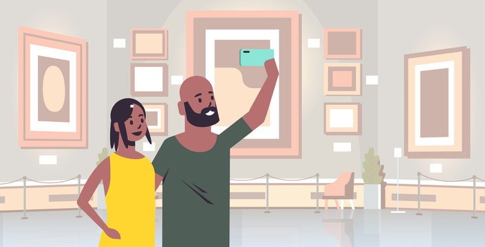young couple taking selfie photo on smartphone camera african american man woman visitors in modern art gallery museum interior portrait horizontal