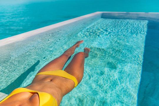 Sexy bikini body woman relaxing swimming in luxury infinity pool of Tahiti resort hotel lying in water floating in yellow bikini. Tanned slim body.