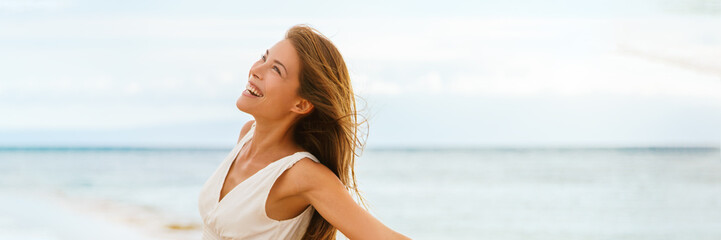 Wall Mural - Happy Asian woman feeling good and free on ocean banner background on beach travel vacation cruise panorama.