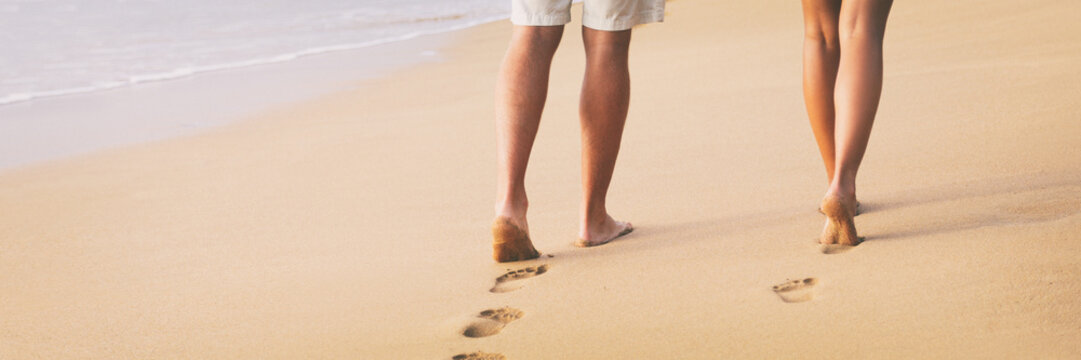 Beach couple walking barefoot on sand at sunset walk honeymoon travel banner - woman and man relaxing together leaving footprints in the sand.