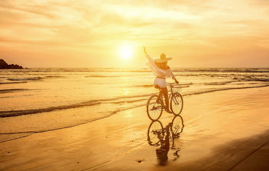 Happiness woman traveler with her bicycle rides on sea coastline Wall mural