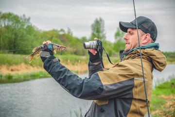 Fisherman photographs caught pike.