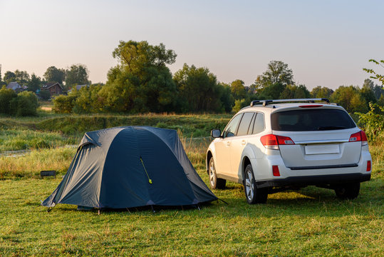 SUV and tourist tent in the camping on the river bank