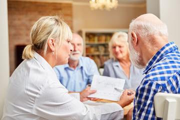 Ärztin betreut Senioren in einer Therapie Sitzung