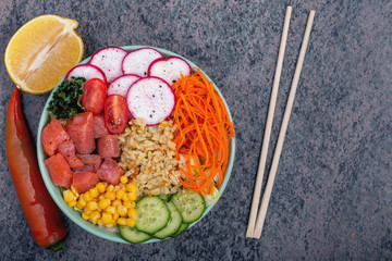 Raw fish, rice and fresh vegetables on wooden background. The concept of natural healthy food