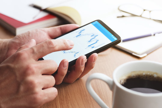 Stock market charts on smartphone screen.Closeup of male hands holding smartphone. Checking financial market.