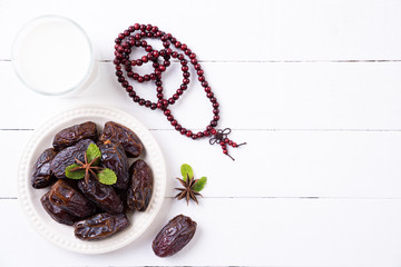 Ramadan food and drinks concept. Wood rosary, milk and dates fruit on a white wooden table background. Top view, Flat lay.