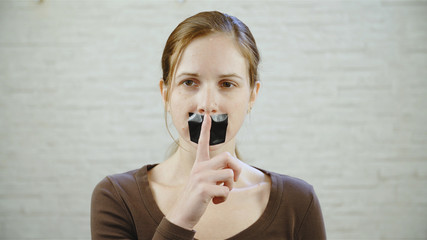 Woman with duck taped mouth