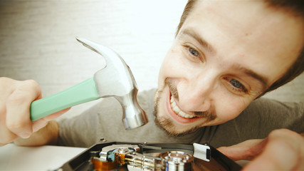 Funny man hammering the inside of hard drive
