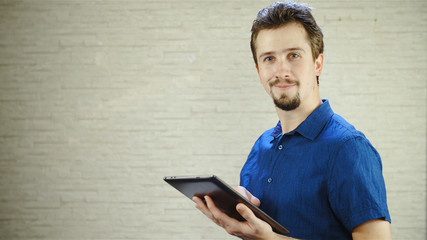 Man with tablet computer in hand smiling into camera