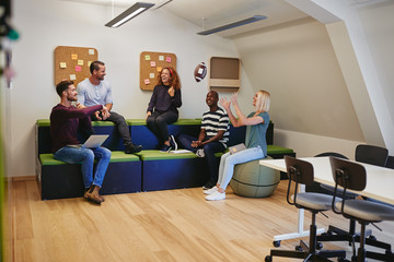 Designers laughing together during a casual meeting in an office