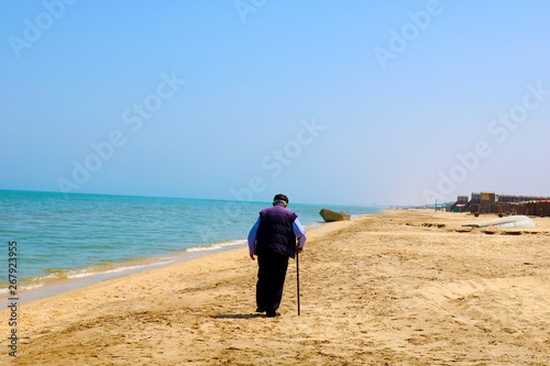An Old Man With A Cane Walks Along The Beach