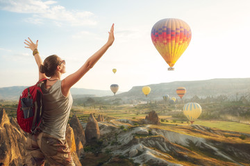 Fototapete - Happy woman traveler with red backpack watching the hot air balloons