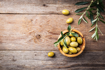 Fresh green olives in a bowl and olive branch on rustic wooden background, top view Wall mural