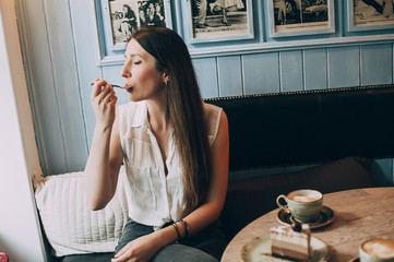 stylish girl drinks coffee and eats cake in a cafe
