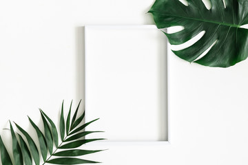 Summer composition. Tropical palm leaves, white photo frame on white background. Summer, nature concept. Flat lay, top view, copy space