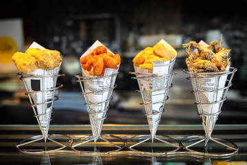 Sea food in cones at counter in small street shop in Spain – snack with mixed takeaway grilled fish and fried seafood – to go delicious roasted octopus, anchovies and calamari ready to eat by tourists