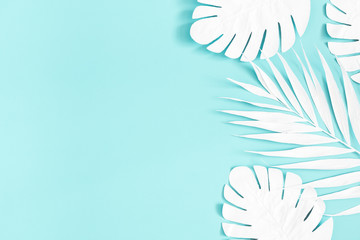 Summer composition. White palm leaves on blue background. Summer concept. Flat lay, top view, copy space