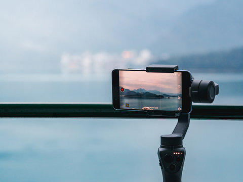 A gimbal stabilizer with mobile phone taking a timelapse of the mountain and lake landscape.
