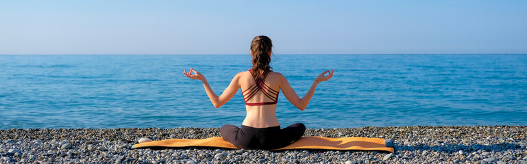 Young slim woman meditating on orange yoga mat back view outdoors at pebble beach by the sea. Yoga at nature concept