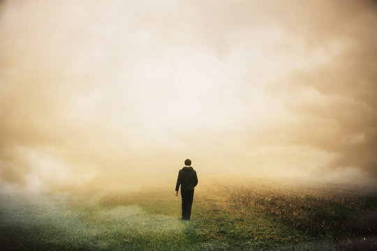 Cloudy misty field with a man