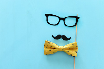 Father's day concept. Hipster glasses and moustache over blue wooden background. top view, flat lay