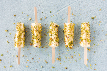 Mango and Pistachio Kulfi Lollies on Blue Cement Background