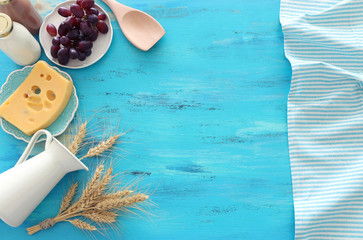 Top view photo of dairy products over blue wooden background. Symbols of jewish holiday - Shavuot