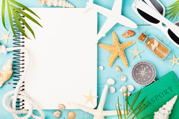 Planning summer holidays, trip, travel and vacation background. Open notebook with accessories on blue table top view. Flat lay style.