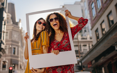 Wall Mural - Girls posing with empty photo frame