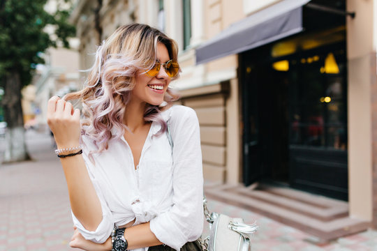 Pretty girl wearing sunglasses and bracelets playing with her short curly hair and smiling on the street. Outdoor portrait of laughing blonde young woman in white shirt standing near store.