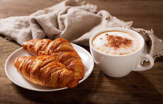 cup of cappuccino coffee and croissants