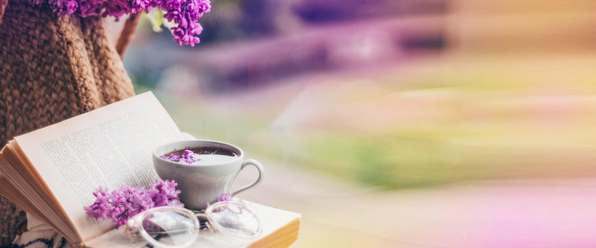 Book, glasses, cup of tea and lilac on a wooden window. Fragrant tea in the garden. Romantic concept. Place for text