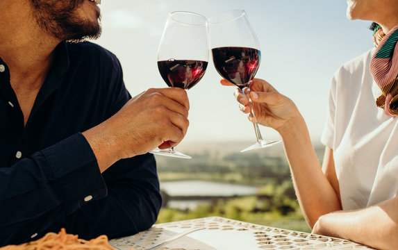Close up of a couple toasting wine