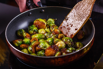 Photo sur cadre textile Bruxelles young woman fries Brussels sprouts on a frying pan