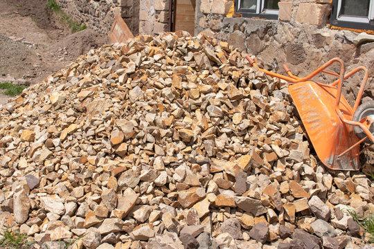 Stones and wheelbarrow near the house under construction