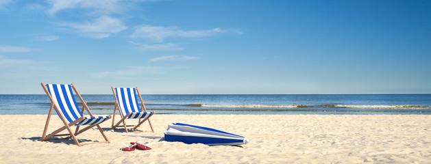 Paar Strand Liegen am Meer mit Sonnenschirm im Sand
