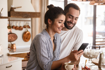 Photo of smiling brunette couple drinking coffee and using cell phone during breakfast at home Wall mural