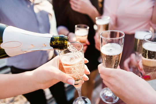 a young company pouring champagne into the wineglasses. young guys drink champagne at sunset. sparkling champagne in glass goblets. splashes of champagne