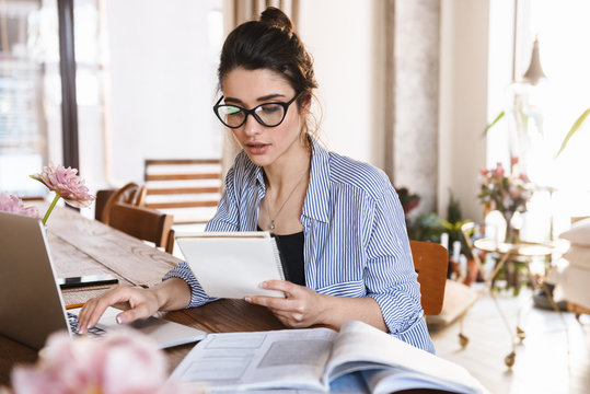 Image of smart brunette woman 20s typing on laptop while working or studying at home