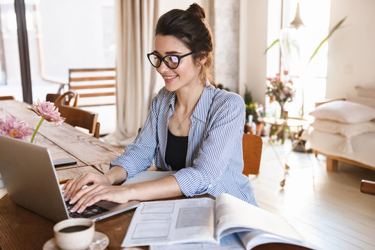 Image of smart positive woman typing on laptop while working or studying at home